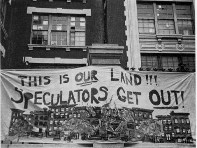 """People holding up sign reading """"The is our land!!! Speculators Get Out!"""""""